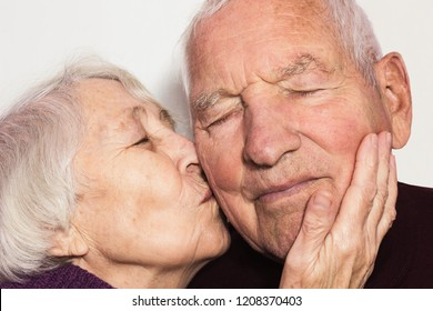 Beautiful senior woman kissing happy man isolated on whita