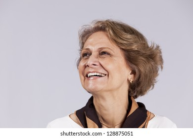 Beautiful senior woman looking up (isolated on gray)