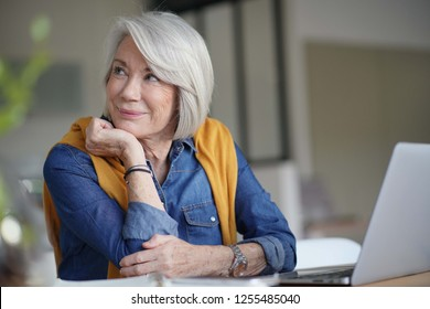 Beautiful senior woman looking pensive at home with laptop