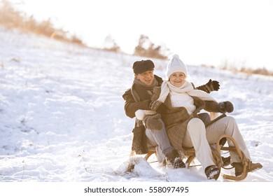 Beautiful senior woman and man on sledge having fun in sunny winter nature.