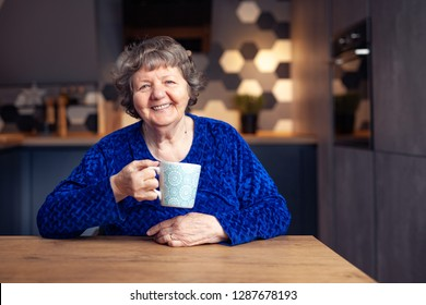 Beautiful senior woman in modern home holding a mug smiling to the camera