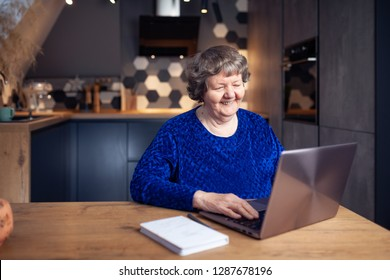 Beautiful senior woman in modern home using a laptop computer