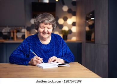 Beautiful senior woman in modern home writing down expenses