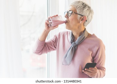 Beautiful senior woman with modern short gray hair and glasses drinking healthy fresh fruit smoothie by the window in her bright home and holding mobile phone in her hand, Healthy natural lifestyle