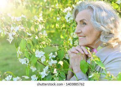 Beautiful senior woman posing near blooming tree