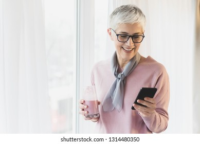 Beautiful senior woman with pretty smile and modern glasses reading message on her phone by the window in her bright modern living room, Bright sunny winter morning