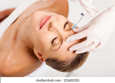 beautiful senior woman receiving cosmetic injection on her forehead