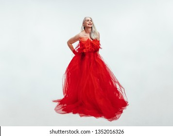 Beautiful senior woman in a red evening gown. Senior woman in an elegant red dress over white background.