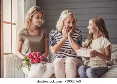 Beautiful senior woman is sitting happily on couch and smiling while her daughter and granddaughter are giving her presents