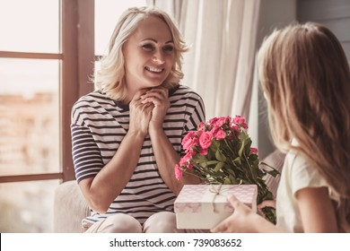 Beautiful senior woman is sitting on couch and smiling while her granddaughter is giving her presents