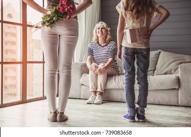Beautiful senior woman is sitting on couch and smiling while her daughter and granddaughter are holding presents for her