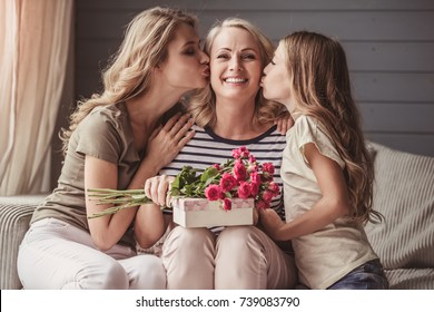 Beautiful senior woman is sitting with presents and smiling while her daughter and granddaughter are kissing her in cheeks