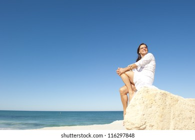 Beautiful senior woman sitting relaxed, joyful and happy on rock at beach, enjoying holiday, retirement at sea, isolated with ocean and blue sky as background and copy space.