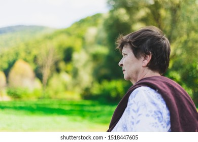 Beautiful senior woman standing alone in nature on a summer day - Sad old lady feeling lonely and looking in the distance while walking in the forest