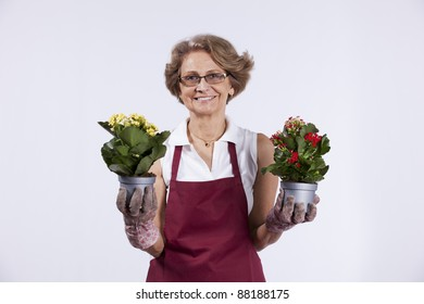 Beautiful senior woman taking care of her flowers