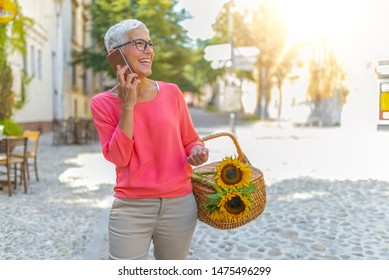 Beautiful senior woman talking on cellphone while walking on the street. Senior woman, on the phone. Happy senior woman calling on smartphone. Retirement, communication and old people concept