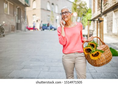Beautiful senior woman talking on mobile phone outdoors. Senior On The Phone. Mature woman using cellphone. Confident senior woman uses smart phone while walking