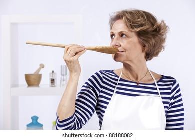 Beautiful senior woman tasting the soup