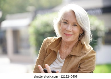 Beautiful senior woman texting outdoors