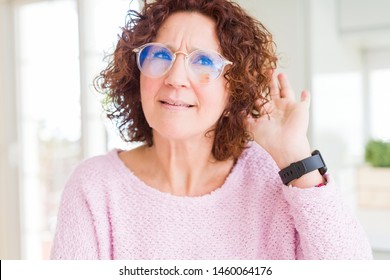 Beautiful senior woman wearing pink sweater and glasses smiling with hand over ear listening an hearing to rumor or gossip. Deafness concept.