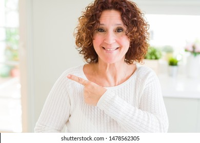 Beautiful senior woman wearing white sweater at home cheerful with a smile of face pointing with hand and finger up to the side with happy and natural expression on face