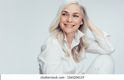 Beautiful senior woman in white casuals looking away and smiling. Cheerful mature woman sitting on white background.