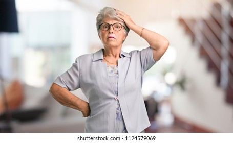 Beautiful senior woman worried and overwhelmed, forgetful, realize something, expression of shock at having made a mistake at home.