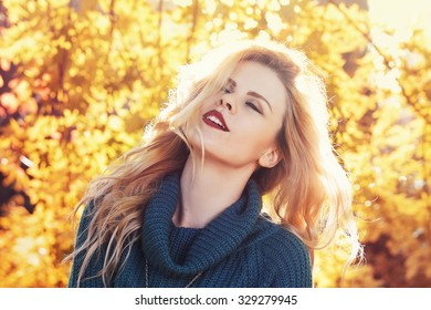 beautiful sensual blond woman with closed eyes on autumn yellow background