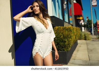 beautiful sensual blonde woman posing in the street in a white summer jumpsuit and lace. Fashion bohemian style photo