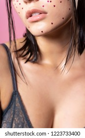 Beautiful sensual brunette girl model wearing a transparent black bra on her big breasts. Close up. Makeup with sparkling glitters in the shape of a hearts. Wet hair. Fashion, commercial, design.