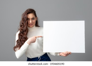 beautiful sensual business woman with long curly hair shows a blank bilboard, isolated on gray, copy space