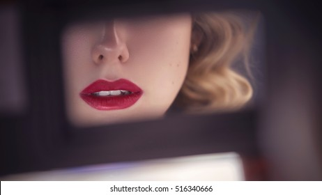 Beautiful sensual caucasian woman with exotic appearance with curled blonde hairstyle and red lips, looking sideways on a rearview mirror in the car. close up of lips