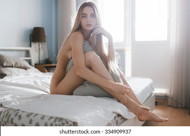 Beautiful sensual girl in the morning on the bed in the room, naked on a sunny day