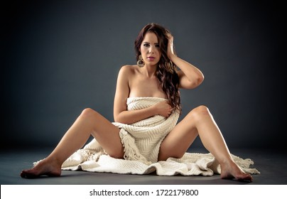 Beautiful Sensual nude woman sits covered by white cloth and hands