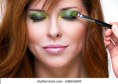 Beautiful sensual red-haired woman. Makeup artist performs makeup on woman's face.
