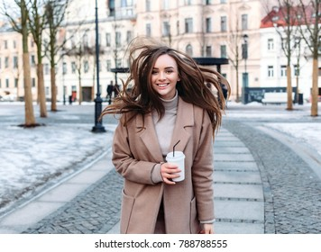 Beautiful sensual stylish happy brunette woman have fun outdoor in winter and posing on the street in winter with a cup of coffee in hands