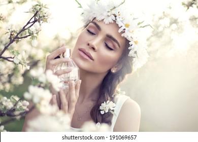 Beautiful sensual woman applying perfume