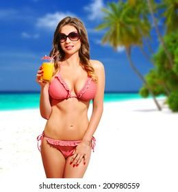 Beautiful sensual woman with bikini, sunglasses and cocktail, on the white sandy beach, Maldives. Half body portrait, long curly blond hair, fashion portrait