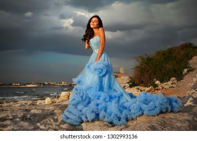 Beautiful, sensual woman in blue dress. Against a cloudy sky and the sea.