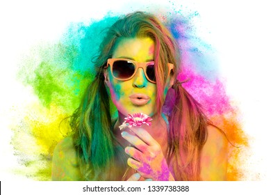 Beautiful sensual woman covered in rainbow colored powder used to celebrate the Holi Festival in March wearing colorful sunglasses and nude lipstick blowing gently a flower in a beauty spring concept
