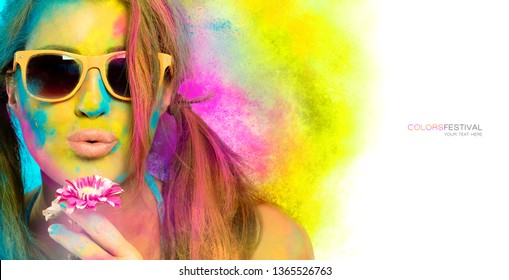 Beautiful sensual woman covered in rainbow colored powder used to celebrate the colors festival wearing colorful sunglasses and nude lipstick blowing gently a flower in a beauty spring concept