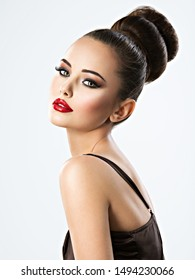 Beautiful sensual woman with creative hairstyle. Pretty young adult girl with brown eye makeup and red lips