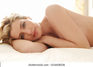 Beautiful sensual woman laying on bed in sunny window bedroom at home naked, looking indoors. Healthy serene female relaxing nude with beauty body figure and perfect skin, female sexy lifestyle.