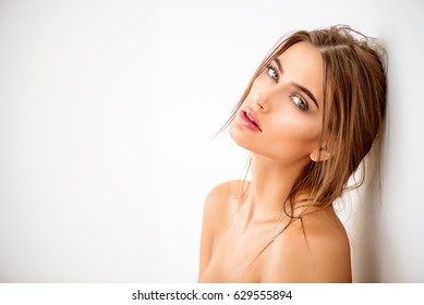 Beautiful sensual woman leaning to a white wall. Beauty, body care concept. Spa, beauty shop.