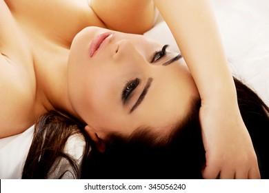 Beautiful sensual woman lying on bed.