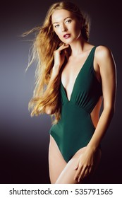 Beautiful sensual woman with magnificent long hair posing in swimsuit. Beauty, fashion. Make-up.