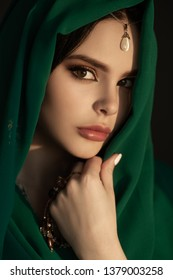 Beautiful sensual woman in traditional costume. Romantic portrait of young girl with perfect bright makeup wearing traditional jewelry standing indoors against dark background. The model lookind at