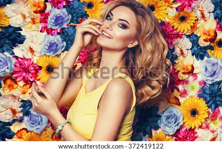 Beautiful sensual woman in yellow dress and bracelet on colorful wall of flowers. Fashion photo, nice hair