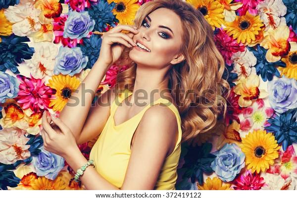花のカラフルな壁に黄色いドレスとブレスレットを着た美しい官能的な女性。ファッション写真、素敵な髪