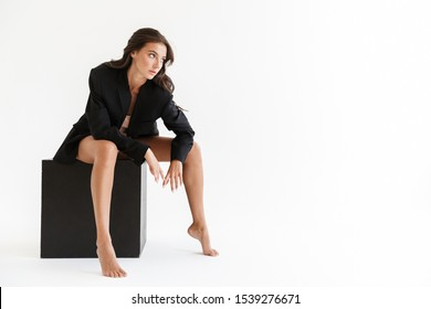 Beautiful sensual young brunette woman wearing oversize jacket posing isolated over white background